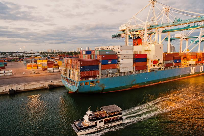 Miami, los E.E.U.U. - 1 de marzo de 2016: el buque de carga y el barco de placer en envase marítimo viran hacia el lado de babor  imagen de archivo