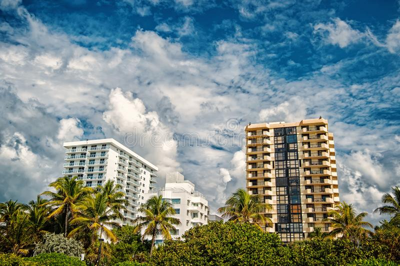 Houses on cloudy sky in miami, usa. Apartment or hotel buildings in garden with green palm trees. Architecture and real. Mi south beach. Houses on cloudy sky in stock photography