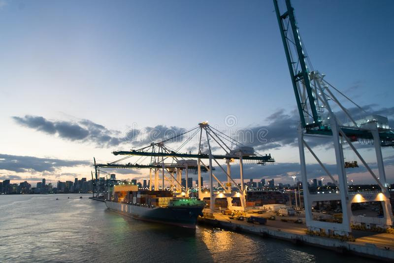 Miami, USA - March 01, 2016: cargo ship and cranes in sea port on evening sky. Maritime container port or terminal. Shipping freig stock photography