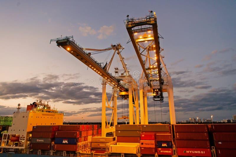 Miami USA - mars 01, 2016: kranar och lastbehållare som staplas i port Behållareport eller terminal med natt royaltyfri fotografi