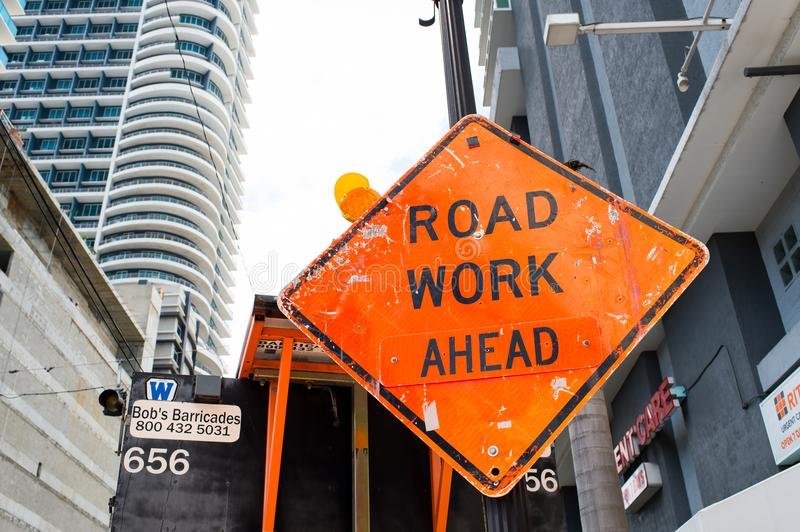 Miami, USA - October 30, 2015: construction sign on city road. Road work ahead warning and safety. Transportation traffic and trav royalty free stock photography