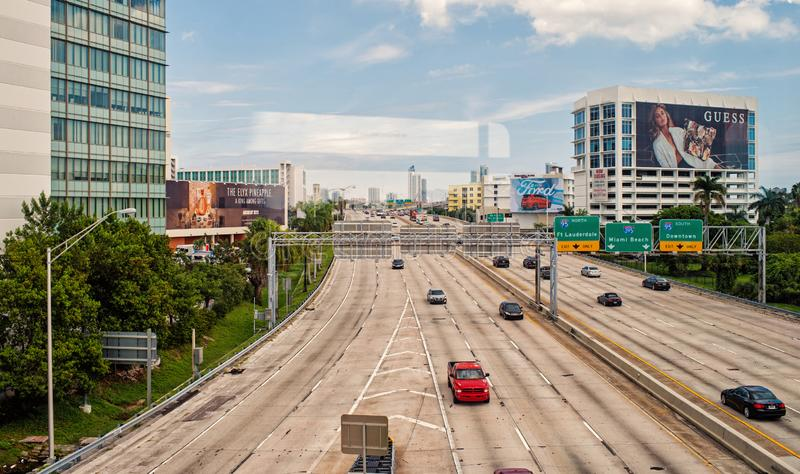 Miami, USA - October 30, 2015: highway or roadway with cars and skyscrapers on cloudy blue sky. Road with traffic signs stock images