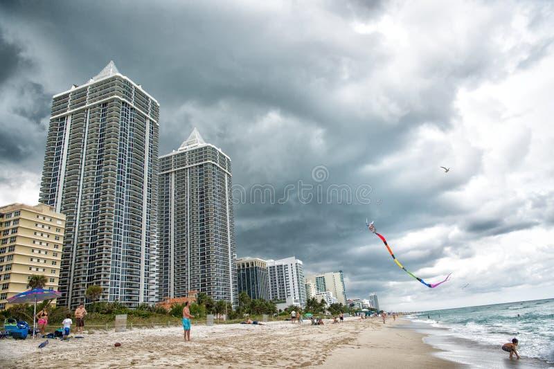 Miami, usa - Styczeń 10, 2016: morze kania i plaża latamy w chmurnym niebie Budynki mieszkaniowi na tropikalnej brzegowej archite zdjęcie stock