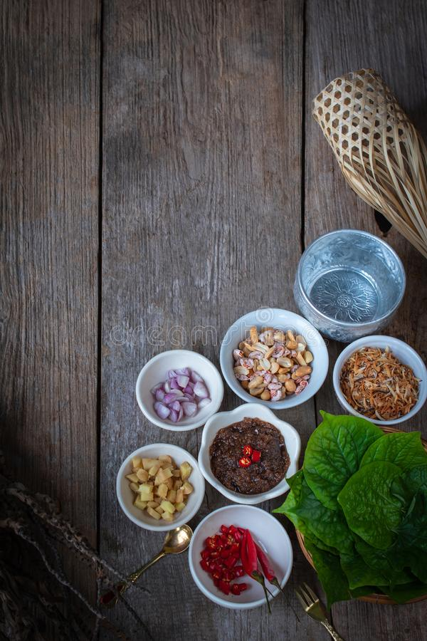 Miang kham,A royal leaf wrap appetizer Consist of Shallot, Ginger, Fried beans, Slice of lemon, Betel leaf, Chilli, Fried coconut stock photography