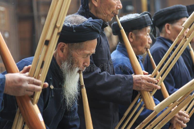 Miao män som spelar en traditionell flöjt i den Langde Miao byn, Guizhou landskap, Kina royaltyfri fotografi
