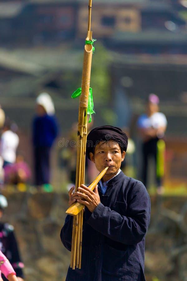 Miao Minority Man Playing Wood Flute Instrument. Xijiang, China - September 15, 2007: Miao ethnic minority man playing a tall bamboo flute instrument at a stock photo