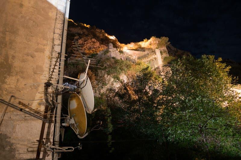 Miasto ściana Kotor Stary miasteczko z antenami satelitarnymi przy nocą, Montenegro obrazy royalty free