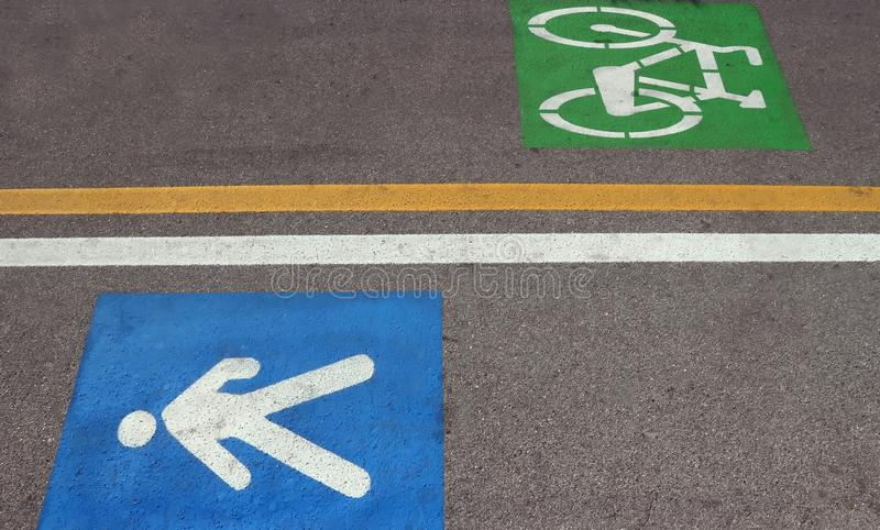 Miasto droga przemian dzieląca w dwa: zwyczajny z błękitem tylko malował znaka i kolarstwa pas ruchu z zielonym symbolem malujący fotografia royalty free