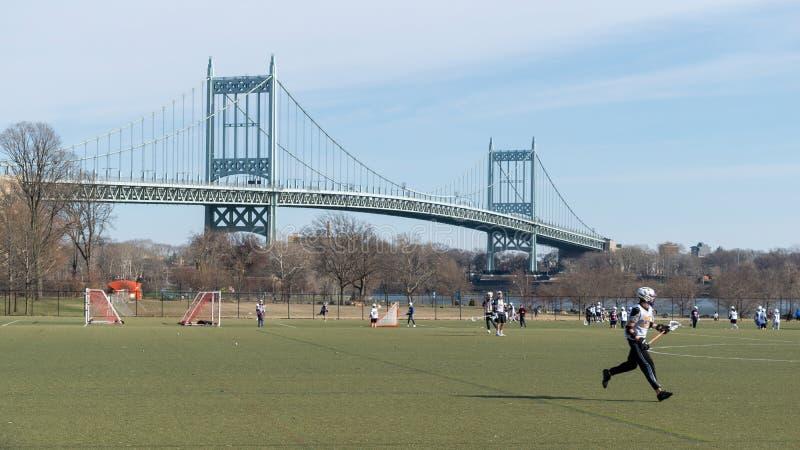 Miasto Nowy Jork, NY/USA - 3/19/2019: Lacrosse drużyna podczas praktyki na Randall wyspie z Triboro mostem w, fotografia royalty free