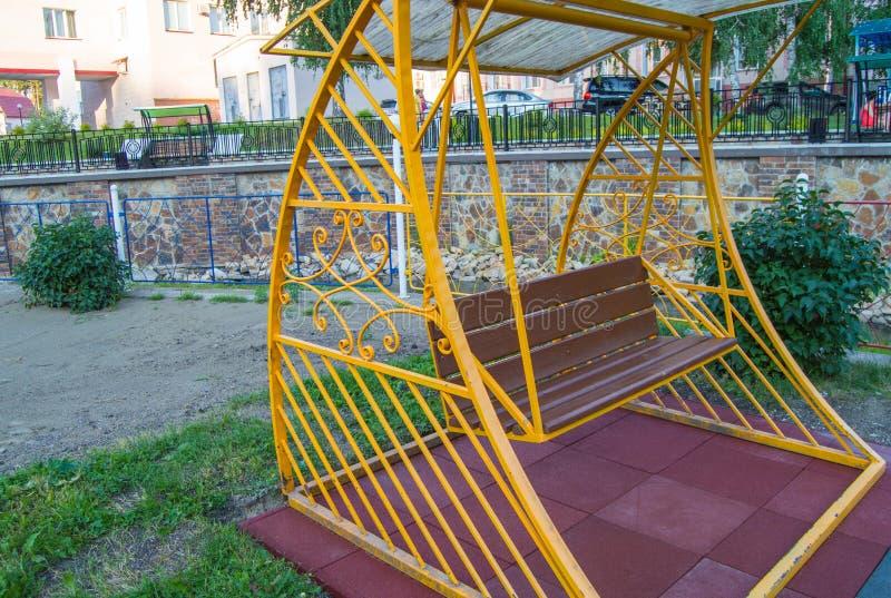 Miasto park w lecie, pusta drewniana huśtawka z żółtą dekoracyjną metal ramą, plenerowy czasu wolnego meble obraz stock
