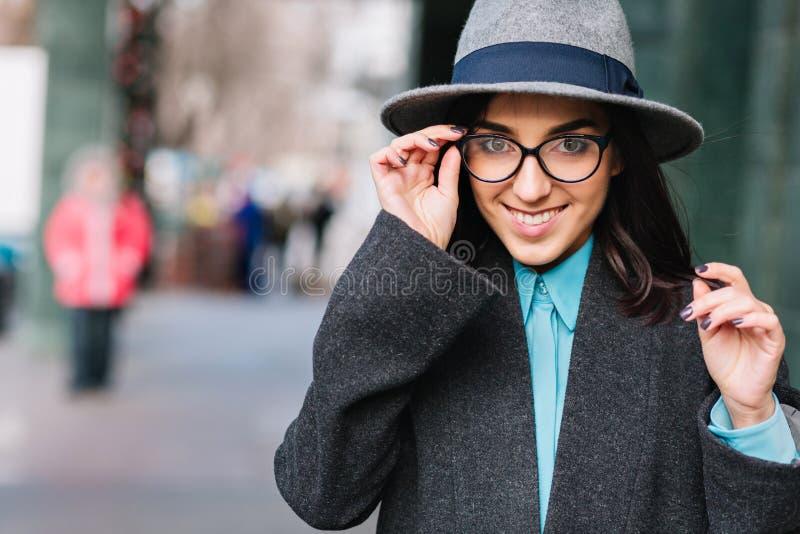 Miasto portreta elegancka powabna młoda kobieta w popielatym żakiecie, kapeluszowy odprowadzenie na ulicie Nowożytni czarni szkła obraz stock