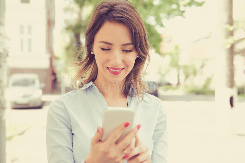 Miasto szczęśliwa młoda kobieta używa telefon komórkowego obrazy stock
