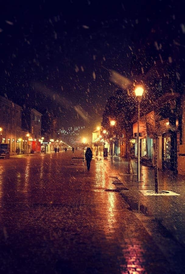 Miasto ulica przy zimy śnieżną nocą z ludźmi chodzić puszyste miast światła snowfall zdjęcia stock