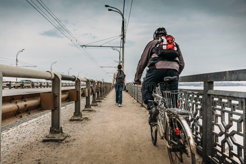 Miastowa scena przy miasto mostem: rowerzysta na bicyklu i podróżniku z plecakiem, widok od plecy, podróży pojęcie zdjęcia stock