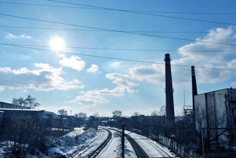 Miastowy krajobraz z starą rośliną piszczy sylwetkę, drzewa bez liści, druty, słońce na zimy chmurnego nieba jaskrawym błękitnym  obrazy royalty free