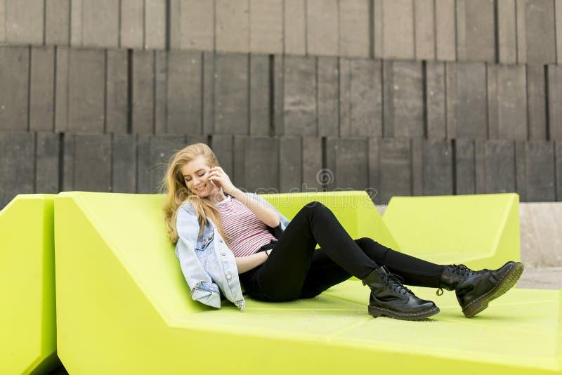 Miastowy młody żeńskiego ucznia siedzący outside i używa telefon zdjęcia royalty free