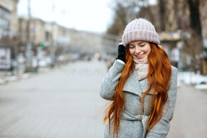 Miastowy portret szczęśliwa imbirowa kobieta z długie włosy być ubranym ciepły zdjęcia royalty free