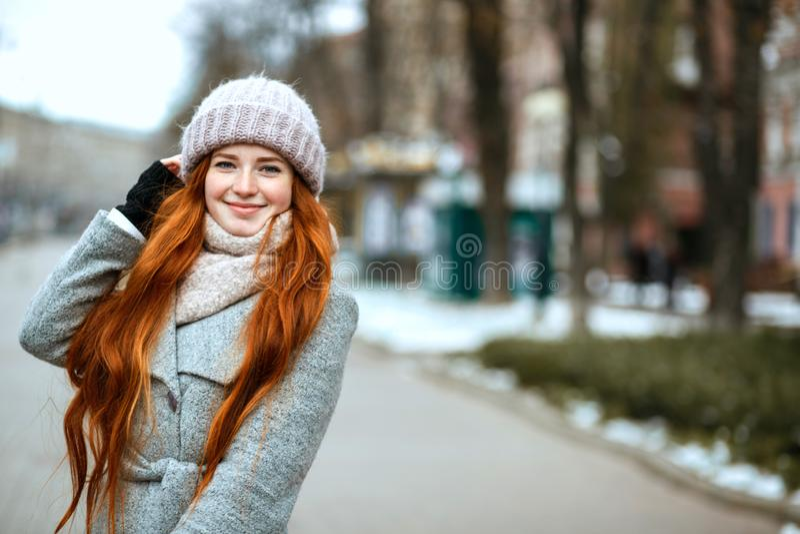 Miastowy portret szczęśliwa rudzielec kobieta z długie włosy jest ubranym wojną obrazy stock