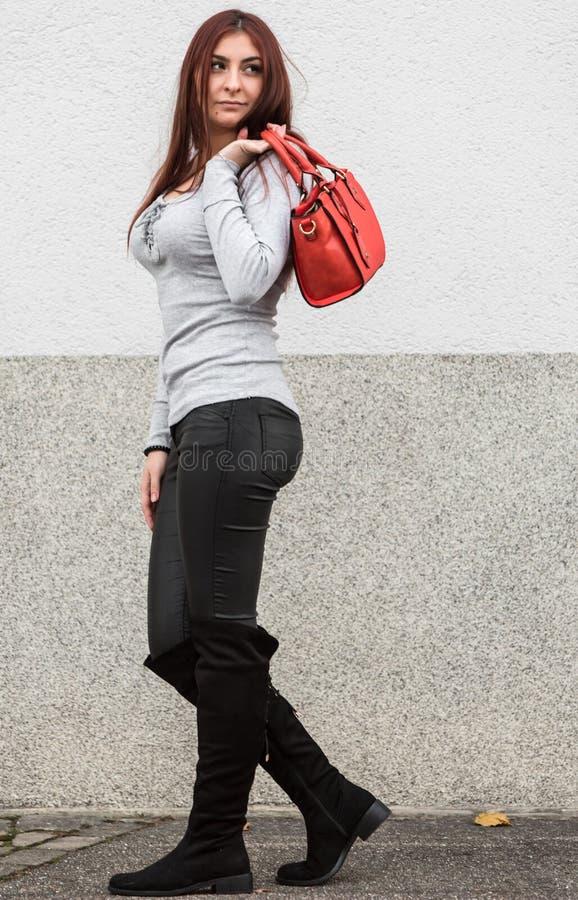 Miastowy styl życia - młoda, piękna, naturalna kobieta z czerwoną torebką, chodzi na ulicie w mieście fotografia royalty free