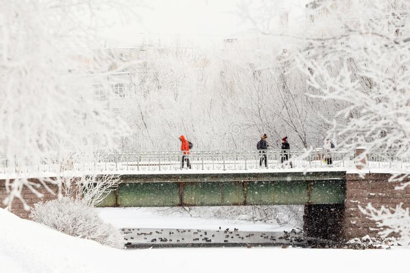 Miastowy zima krajobraz - ludzie na moście podczas ciężkiego dziennego opad śniegu zdjęcia stock