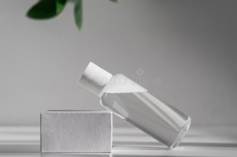Micellar water, makeup remover mockup side view. Natural cosmetology product, organic cosmetics poster concept. Moisturizing. Lotion bottle with leaves on stock photography