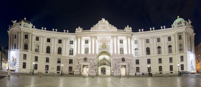从Michaelerplatz看见的霍夫堡宫,全景夜视图 库存照片
