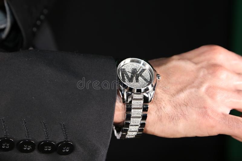 Wealthy business man wearing Micheal Kors luxury watches. Micheal Kors, the luxury designer, has men styling with diamonds on watches in business, and it`s not stock photography