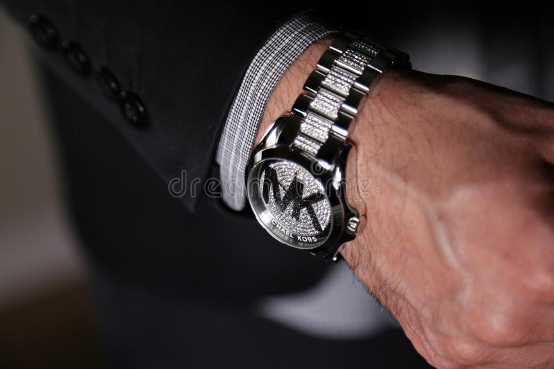 Wealthy business man wearing Micheal Kors luxury watches. Micheal Kors, the luxury designer, has men styling with diamonds on watches in business, and it`s not stock photo