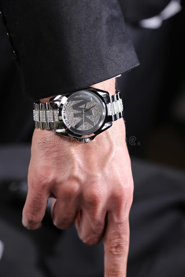 Wealthy business man wearing Micheal Kors luxury watches. Micheal Kors, the luxury designer, has men styling with diamonds on watches in business, and it`s not stock image