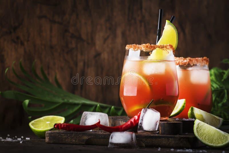 Michelada - mexicansk alkoholiserad coctail med öl, limefruktfruktsaft, tomatfruktsaft, kryddig sås och kryddor, tappningträbakgr arkivfoto