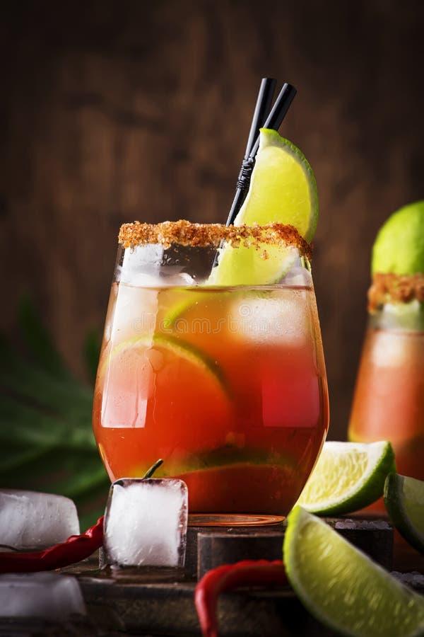 Michelada - mexicansk alkoholiserad coctail med öl, limefruktfruktsaft, tomatfruktsaft, kryddig sås och kryddor, tappningträbakgr royaltyfri fotografi