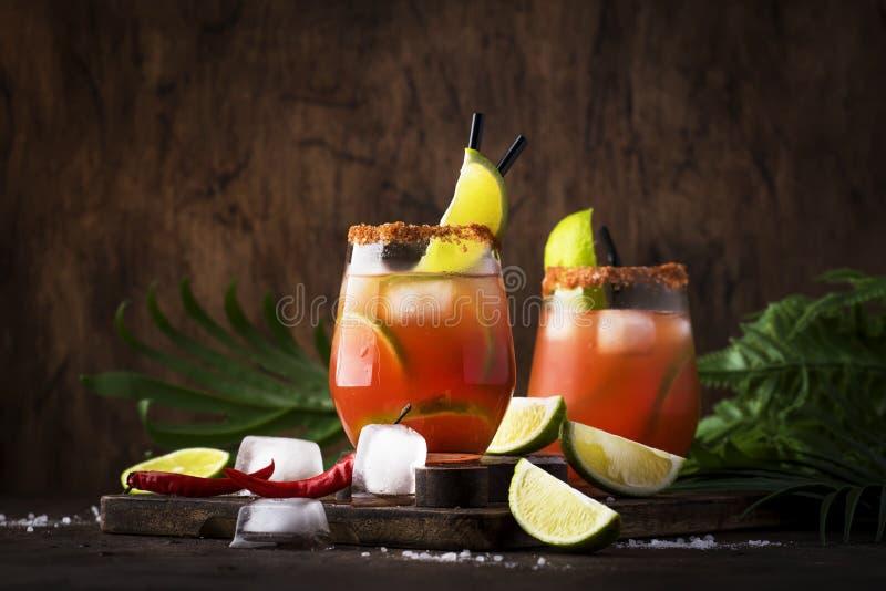 Michelada - mexicansk alkoholiserad coctail med öl, limefruktfruktsaft, tomatfruktsaft, kryddig sås och kryddor, tappningträbakgr royaltyfri bild