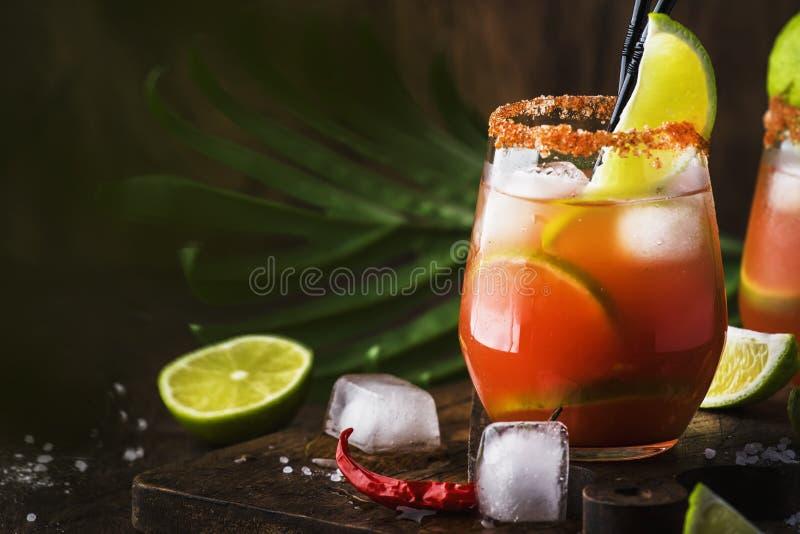 Michelada - mexicansk alkoholiserad coctail med öl, limefruktfruktsaft, tomatfruktsaft, kryddig sås och kryddor, tappningträbakgr arkivbild