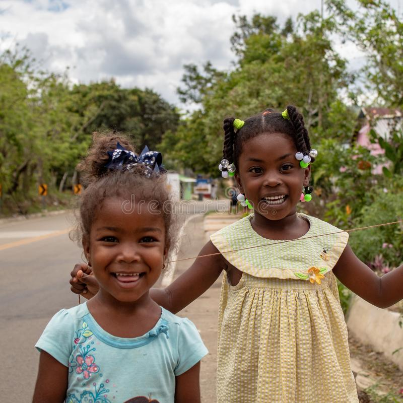 Miches, Dominikanische Republik, am 16. April 2019/zwei junge lokale farbige Mädchen, die mit baloons auf der Seite der Straße sp lizenzfreie stockbilder