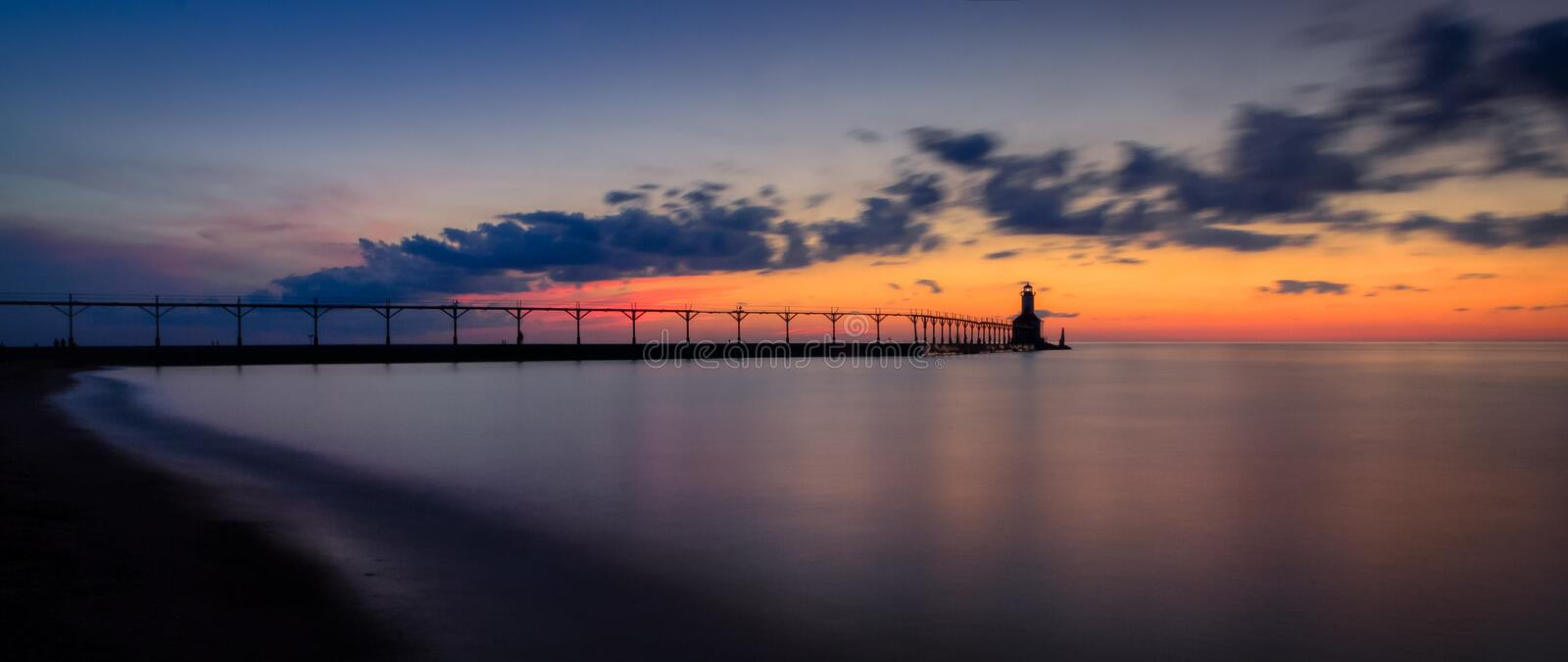 Michigan City East Pierhead Lighthouse After Sunset Panorama. Long exposure panorama of Michigan City East Pierhead Lighthouse after sunset with colorful sky and royalty free stock images
