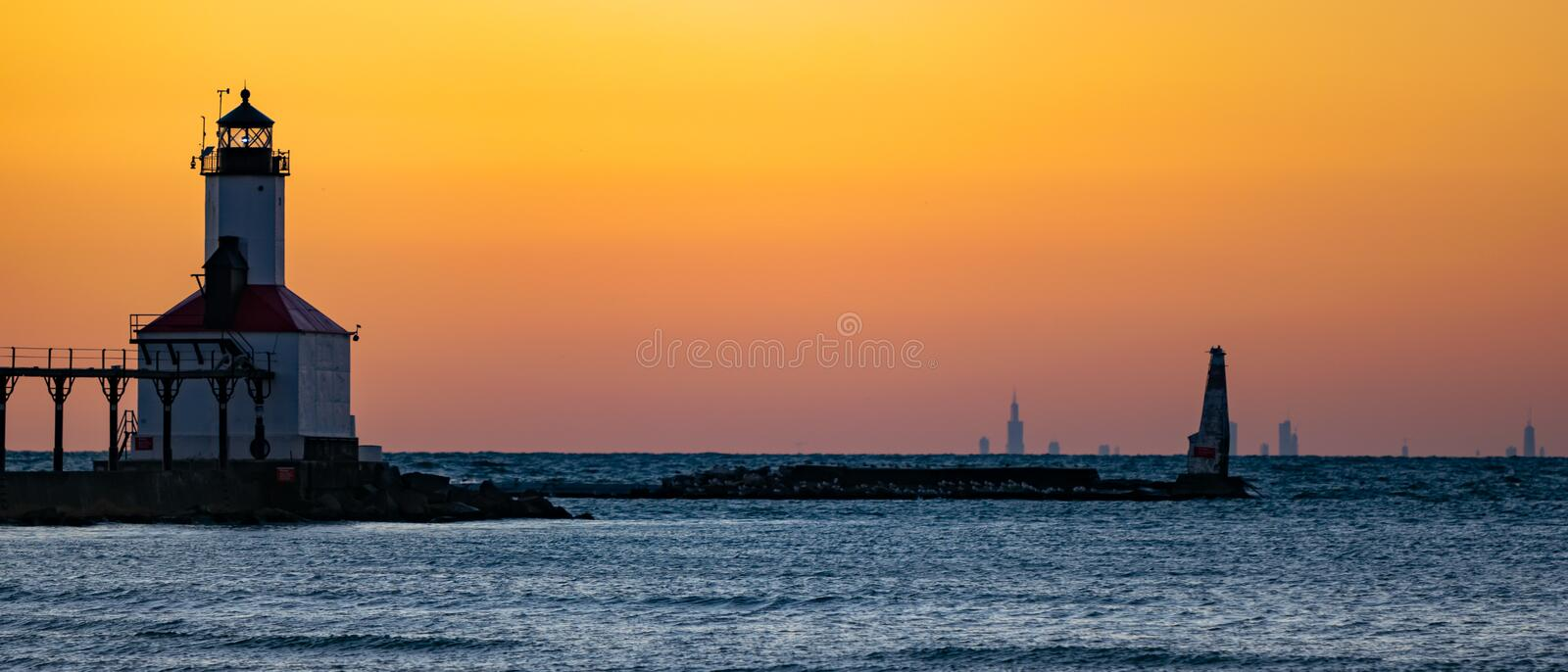 Michigan City, Indiana  : 03/23/2018 / Washington Park Lighthouse during golden hour sunset on the Great Freshwater Lake Michigan. With the City of Chicago on royalty free stock photography
