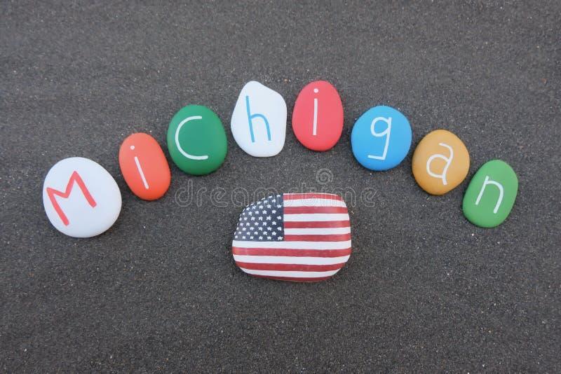 Michigan, Estados Unidos da América, lembrança com as pedras coloridas sobre a areia vulcânica preta fotos de stock
