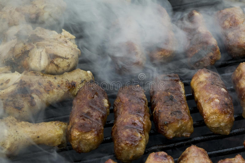 Mici and chicken legs on grill royalty free stock photos