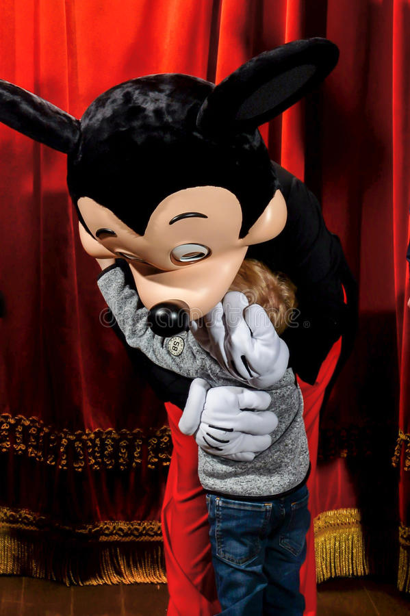 Mickey Mouse at Disneyland Resort Paris. Marne-la-Vallee, France - March 10, 2017 : A child giving a hug to Mickey Mouse at Disneyland Resort Paris. You can find royalty free stock photography