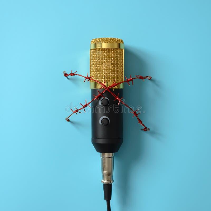 Micrófono amarillo con alambre de púas rojo Concepto para el tema de la censura o de la libertad de prensa foto de archivo