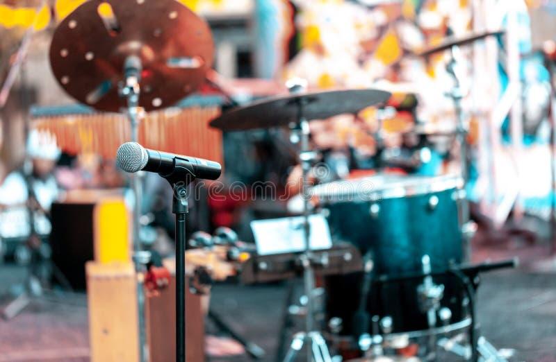 Micrófono con los tambores y otros instrumentos musicales en una etapa al aire libre para realizar música Foco en el micrófono, b imagenes de archivo