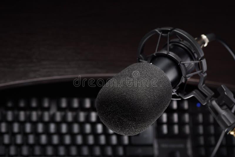 Micrófono de condensador negro del estudio el otro teclado de ordenador foto de archivo