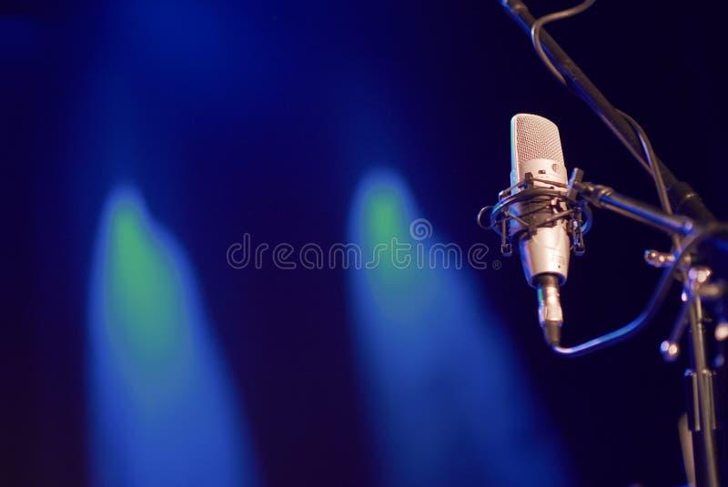 Micrófono de la voz en una etapa con las luces del fondo imagen de archivo