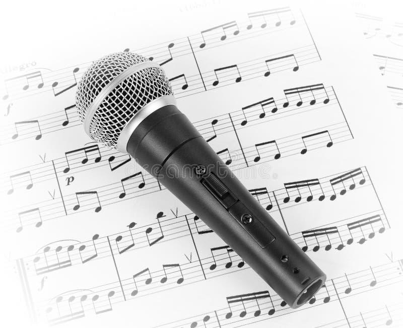 Micrófono dinámico en la hoja de música imagen de archivo libre de regalías