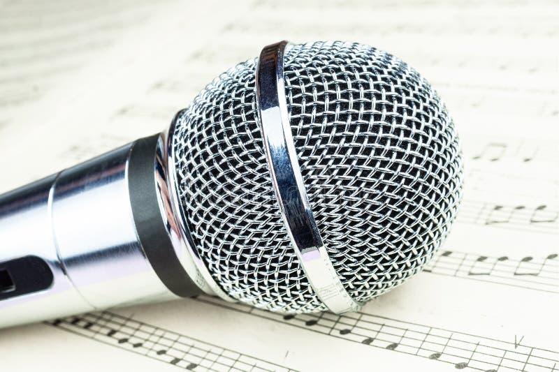 Micrófono dinámico en la hoja de música fotos de archivo libres de regalías
