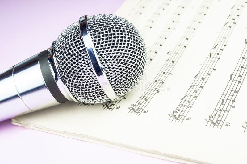 Micrófono dinámico en la hoja de música foto de archivo