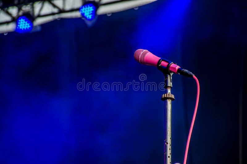 Micrófono en etapa contra un fondo de la etapa del concierto imagen de archivo