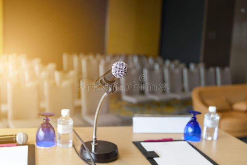 Micrófono en la tabla encima borrosa de fondo del seminario vacío o de la sala de conferencias foto de archivo