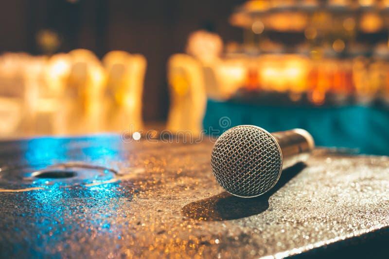Micrófono en la tierra y la foto borrosa de la sala de conferencias o de la sala de seminarios o de casarse el fondo del sitio fotografía de archivo libre de regalías