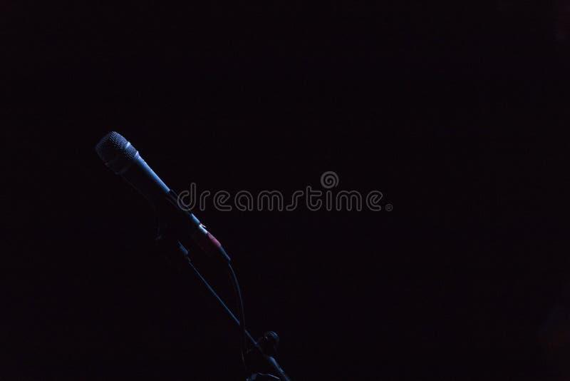Micrófono en su base, en fondo negro con la luz que lo delinea imagen de archivo libre de regalías